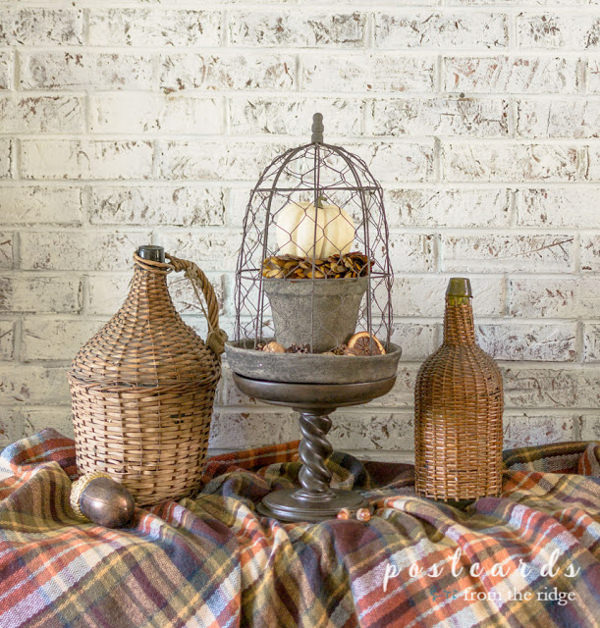 chicken wire fall cloche and wicker demijohns on a plaid blanket scarf
