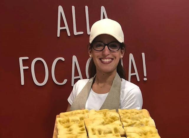 Alice, propietaria sorda de Alis Focacceria, sosteniendo focaccia en la mano