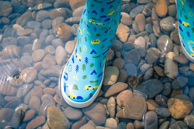 Pair of blue wellington boots paddling in water over pebbles