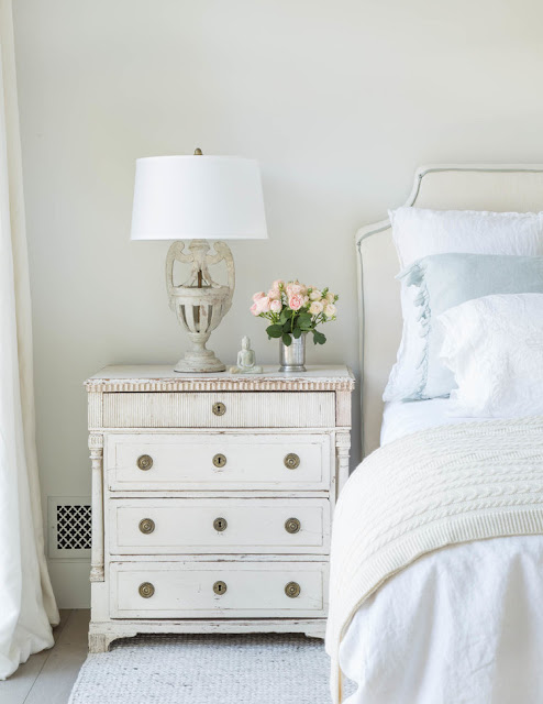 Antique Swedish chest next to beautiful bed in modern farmhouse by Giannetti Home