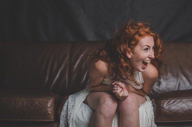 Mulher de vestido branco, sentada em um sofá com a expressão de surpresa
