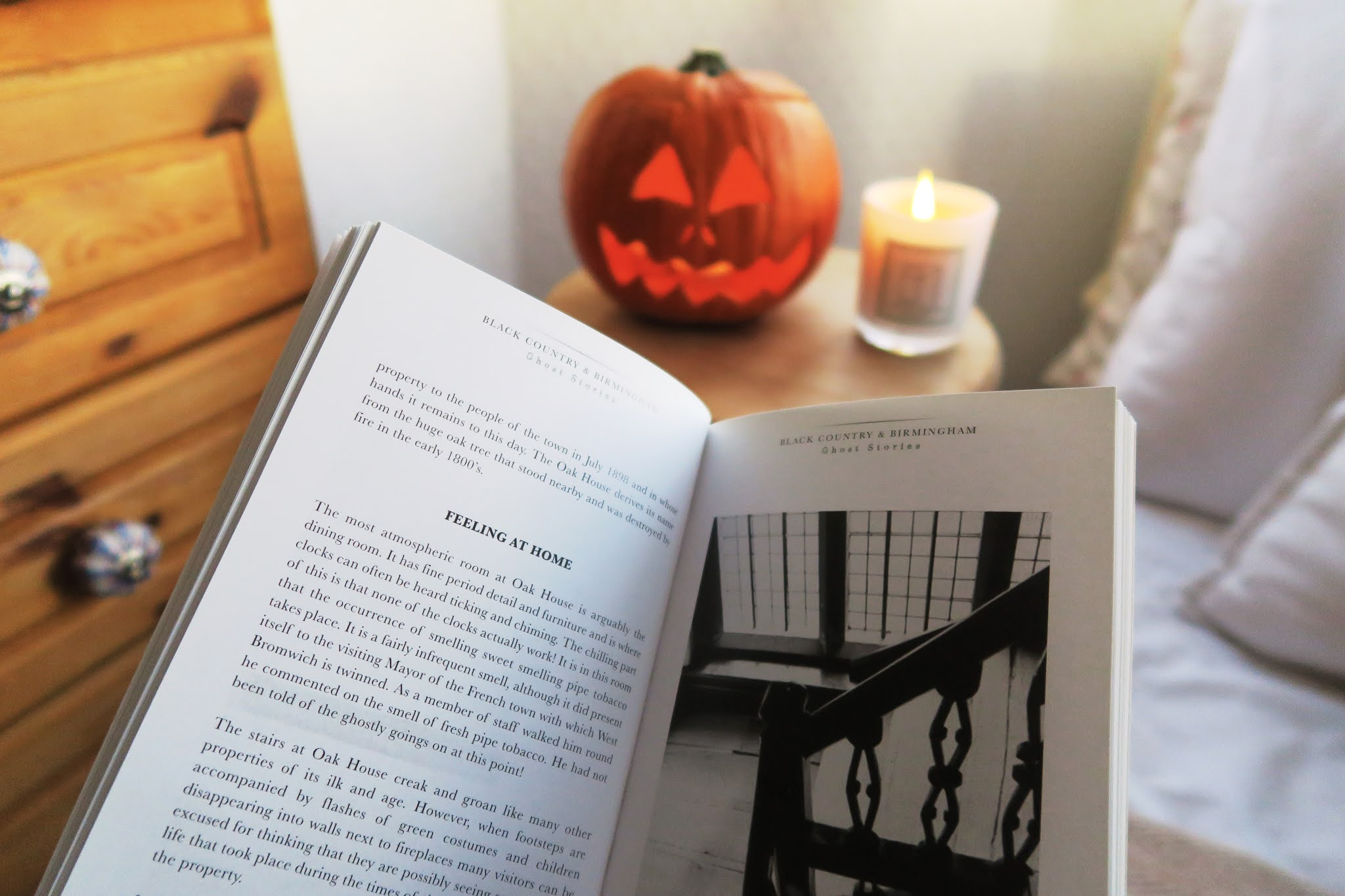 Grace is holding the ghost stories book open. In the background th pumpkin and a lit candle can be seen.