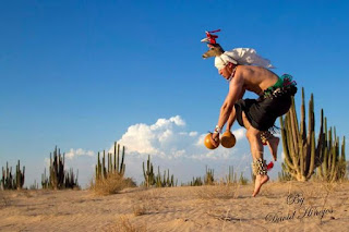 A bare-chested man with a deer headress and a gourd rattle in each hand leaping from the desert floor.A Yaqui Deer Dancer.  Photo by David Hinojos.