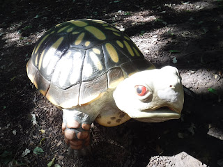 a large, realistically painted turtle sculpture from the nature playscape behind the Dorothy Pecaut Nature Center