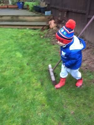 Little boy sweeping the grass