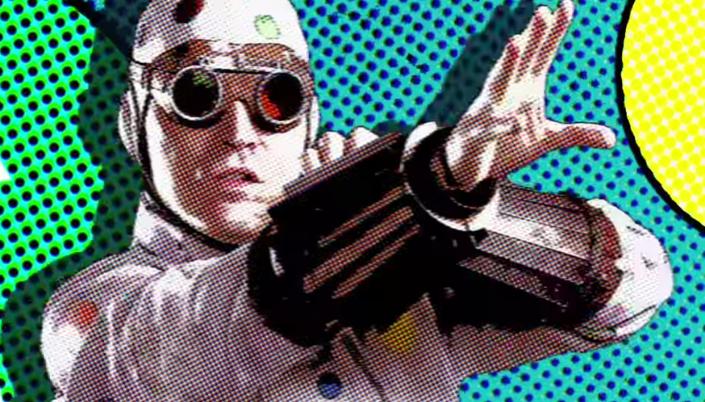 Imagem: fundo em verde e azul com padrão de quadrinhos com o personagem Homem-Bolinha, interpretado por David Dastmalchian, usando um traje branco coberto de bolinhas coloridas e um par de óculos escuros.