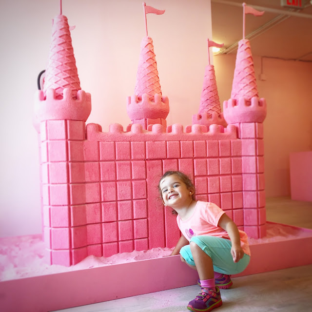 Toddler girl smiles in front of a pink sandcastle