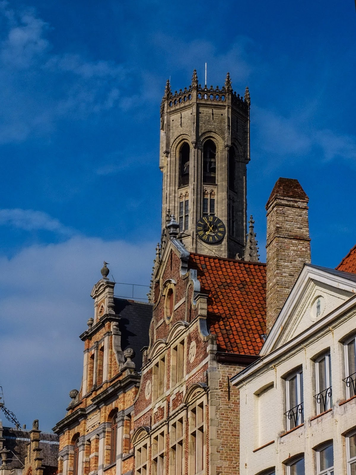 View of the Belfry of Bruges tower from behind other medieval buildings.