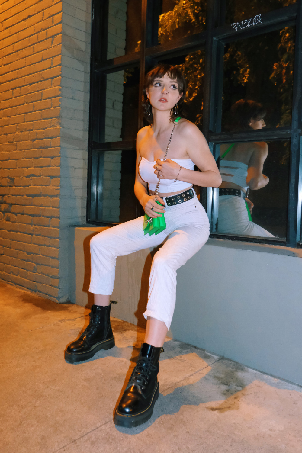 woman in party makeup posing close to the window on the street at night