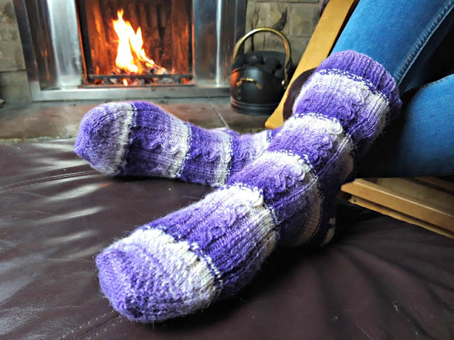 A pair of purple cabled socks being modelled by Christine's feet.  They are resting on a leather footstool in front of an open fire.