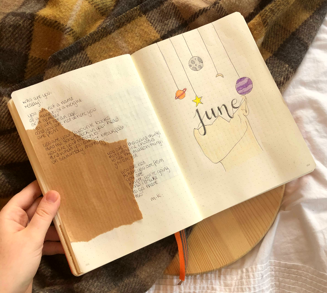 Dotted bullet journal with poetry written on the left hand side and a hand drawn outline of a face under some planets on the right