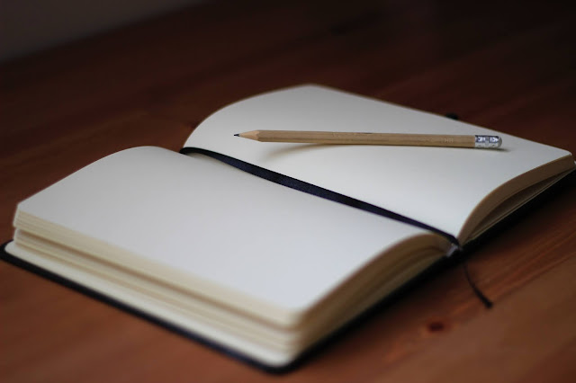 Blank notebook lying open with a pencil on top