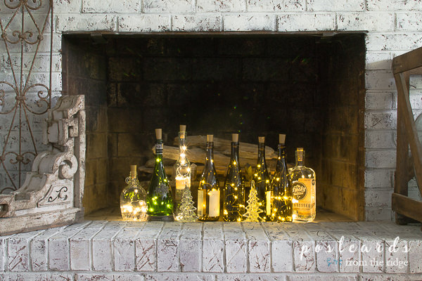 wine bottles with lights inside a fireplace