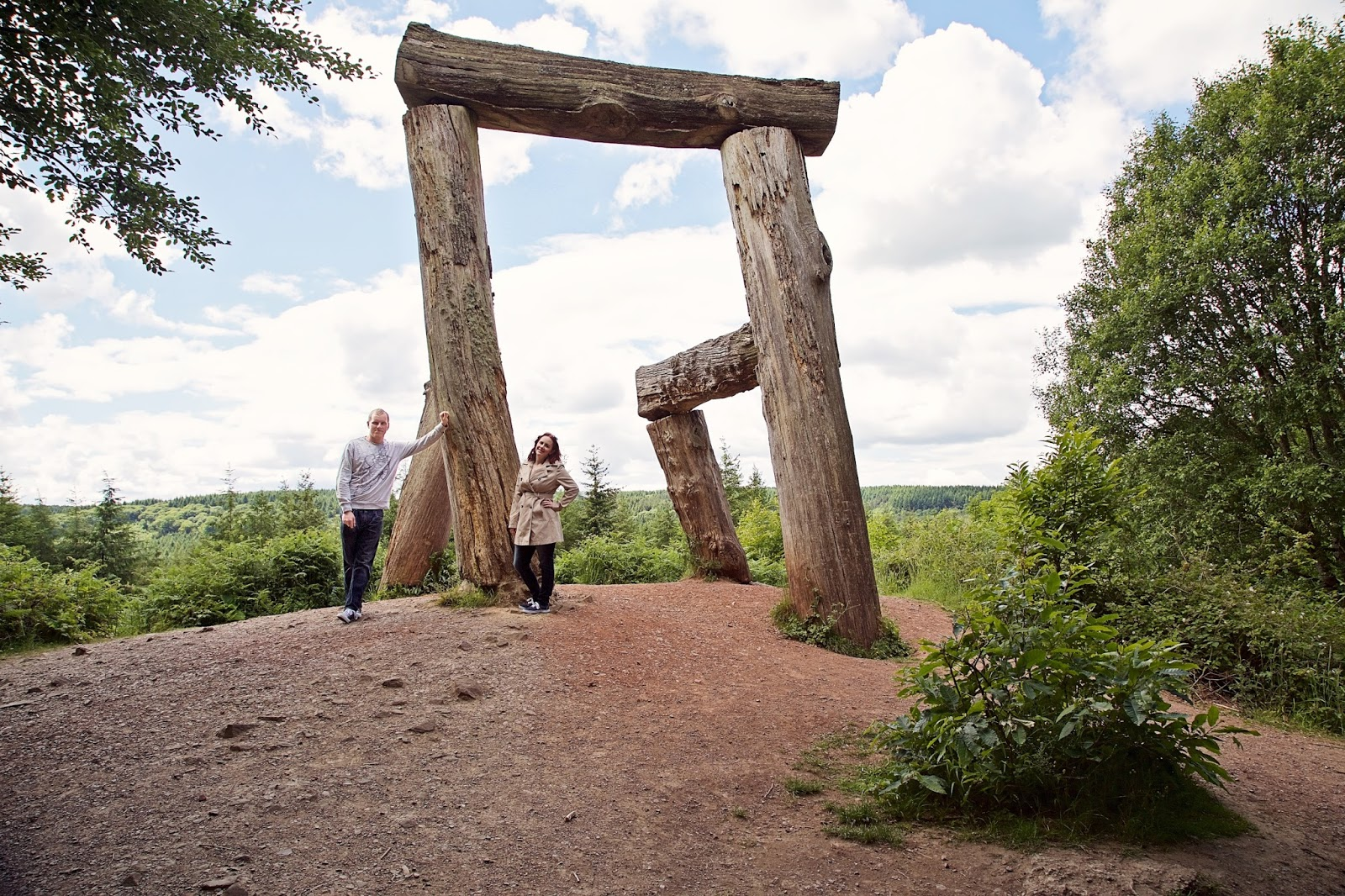 Couple posing in the Forest of Dean next to giant chair sculpture