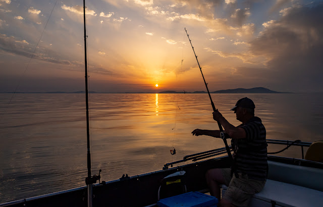 Photo of Phil fishing from Ravensdale's aft deck at sunset