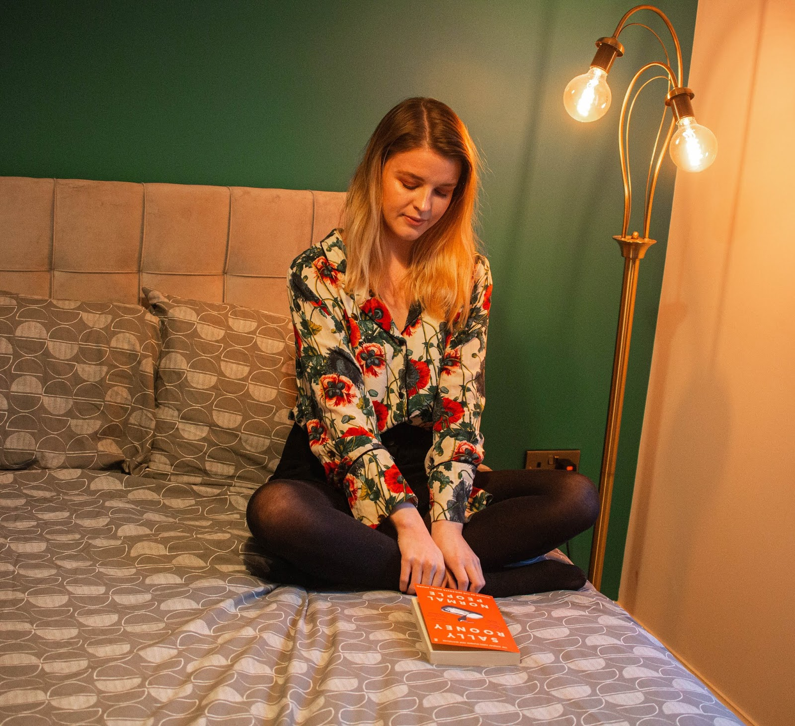 blonde girl chloe harriets sat on bed reading normal people by sally rooney for chloe harriets 2020 book club