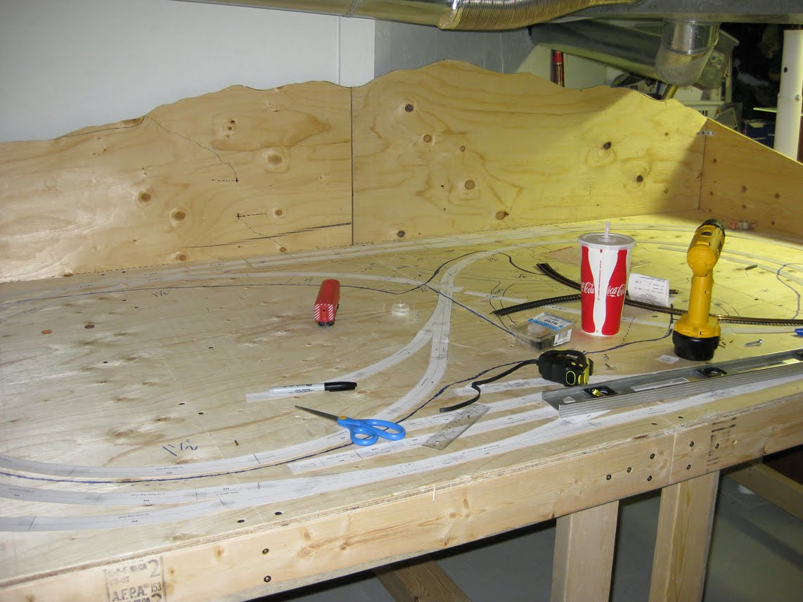 Benchwork made of plywood and lumber with paper track template pieces outlining a railroad track design