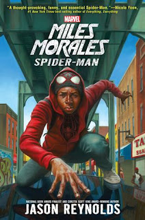 Cover image, 'Miles Morales Spider-Man' by Jason Reynolds. Image depicts a brown-skinned teenager crouching on roadway beneath bridge overpass in city landscape. He is wearing blue pants and a red hooded jacket. Beneath the hood, a face mask - red spider-web pattern against black with red-outlined white eye viewers, is pushed up to reveal his face. He appears to have a determined facial expression.