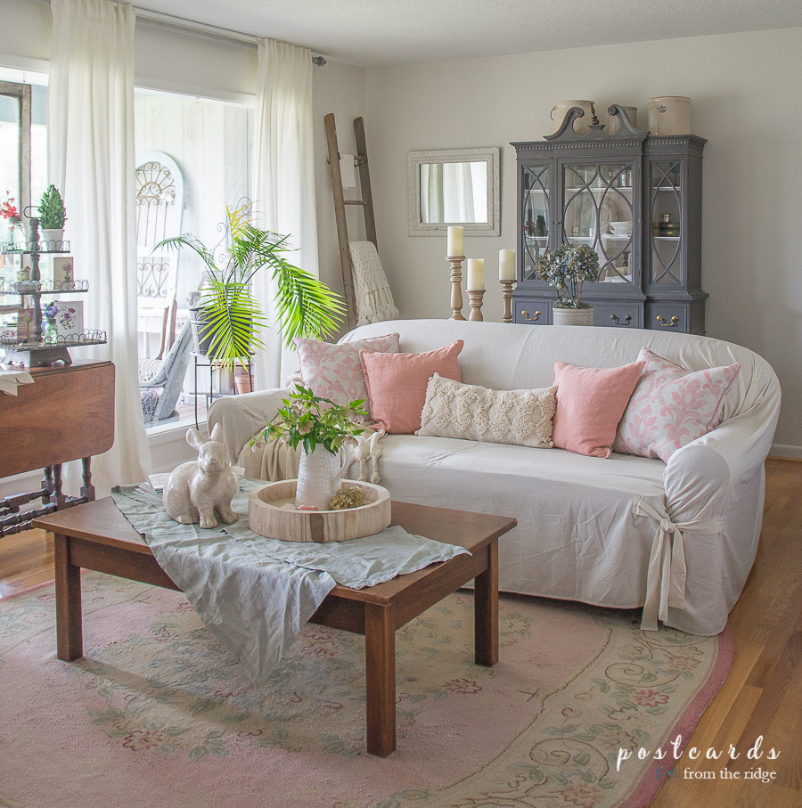 living room with pink rug and pink pillows on a slipcovered sofa