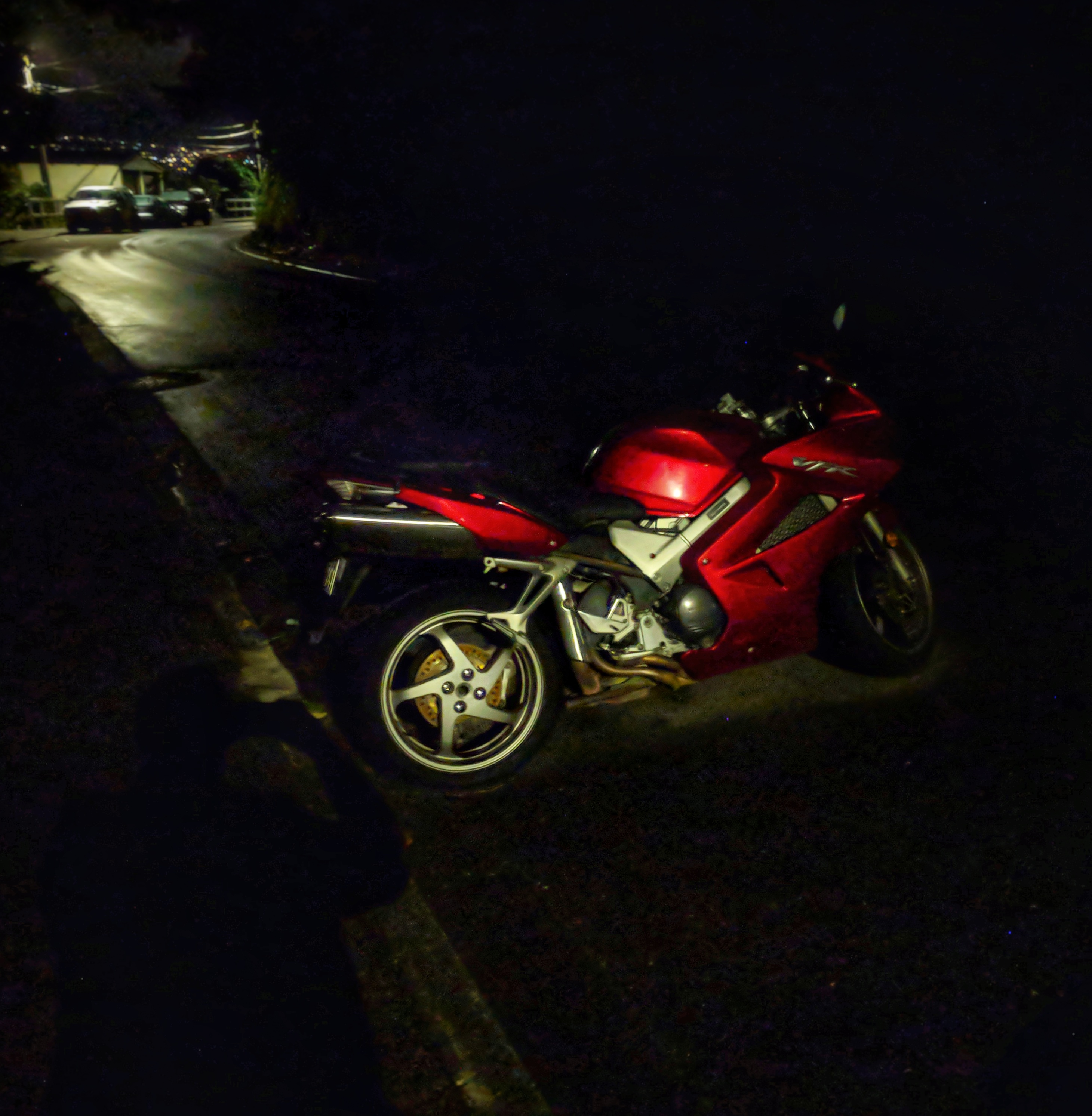 Red motorbike in the shadows of the night