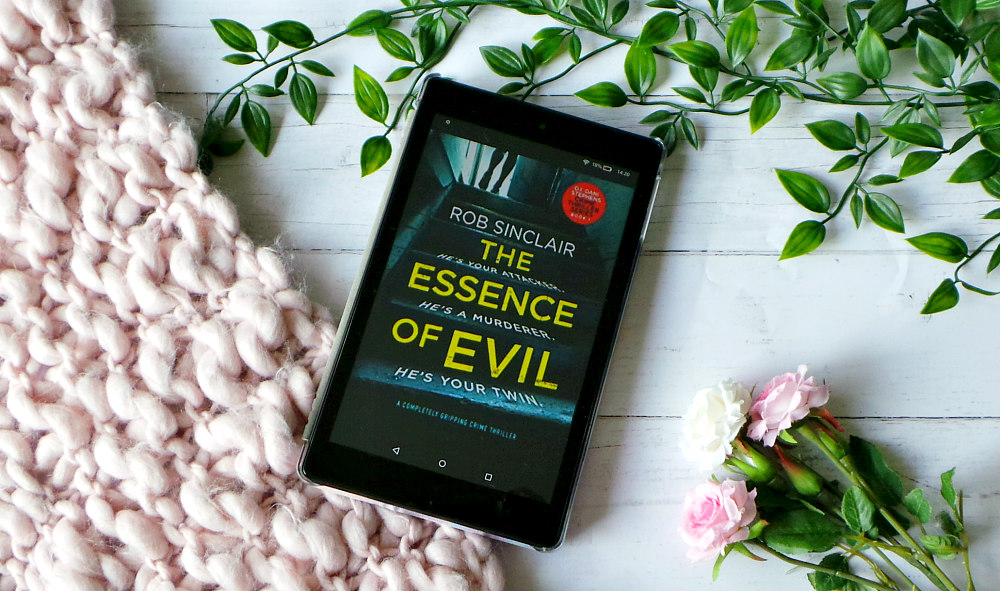 Kindle fire shows the cover of The essence of evil next to a pink chunky knit blanket, leaves and roses. The cover shows a pair of legs at the top of a set of stairs