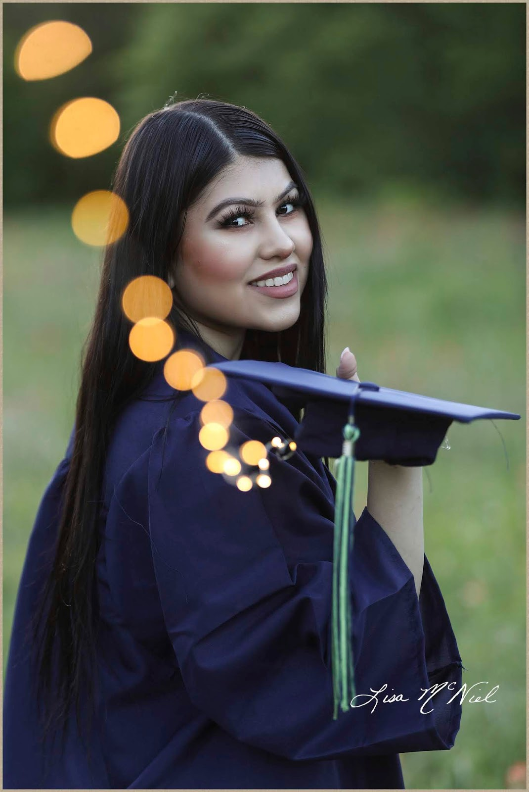 teen girl in graduation gown with fairy lights