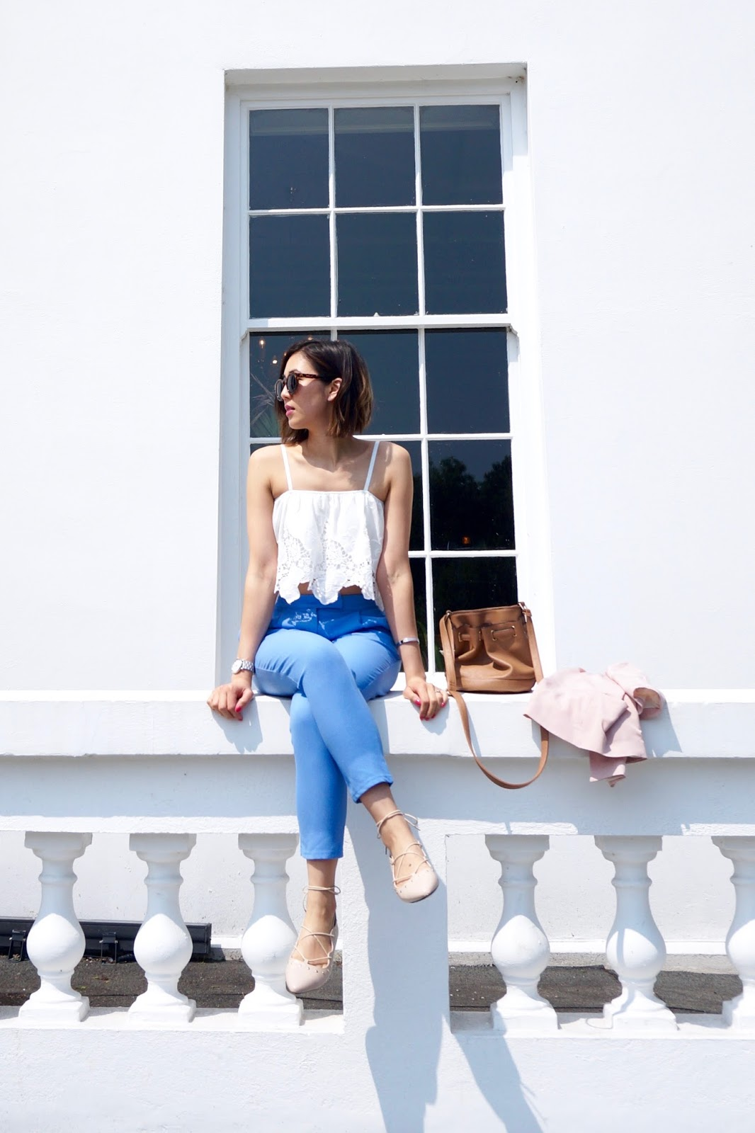 white crochet top and blue trousers