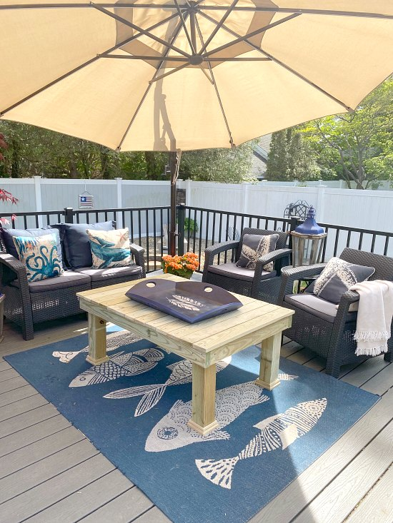 outdoor patio set with large umbrella and fish rug