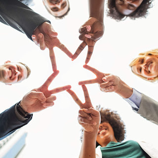 group of people joining fingers to form a star