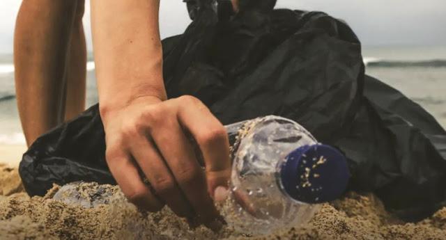 mano che raccoglie bottiglia di plastica sulla spiaggia