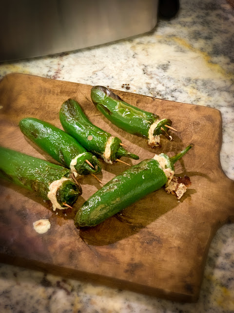 Whole Jalapeno Poppers, a spicy, cheesy, grilled appetizer.  The recipe is straightforward with few ingredients, jalapenos, cream cheese, white cheddar cheese, garlic powder, and of course bacon.