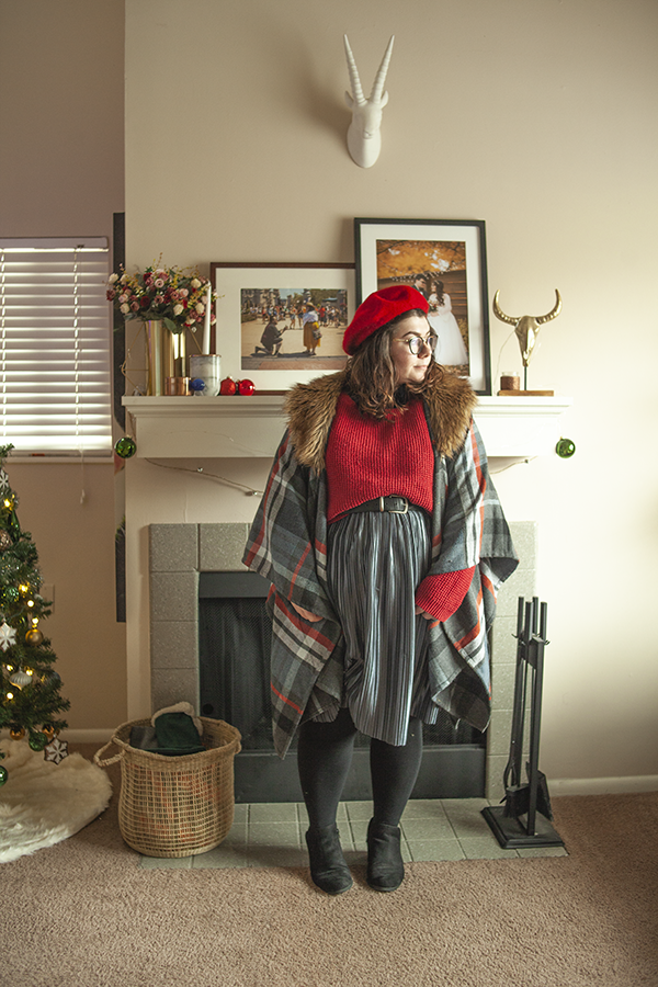 An outfit consisting of a red beret, grey, dark grey, white and red plaid poncho with a brown faux fur collar over a red sweater tucked into a silver blue pleated midi skirt and black ankle boots.