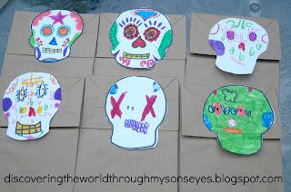 Kids make colored calaveras for Día de los muertos.