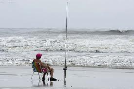 Homem pescando na praia durante o inverno com água fria