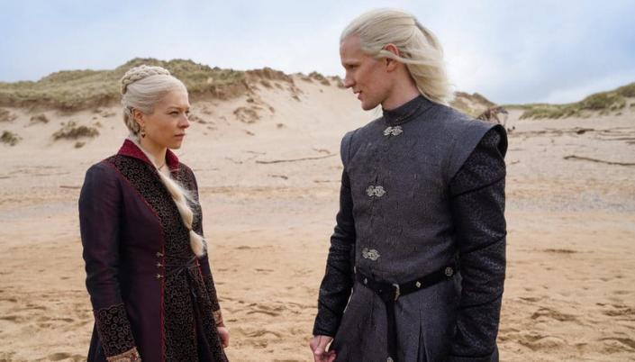 Imagem: Duas pessoas conversam em uma praia. A da esquerda princesa Rhenyra Targaryen. É uma mulher de cerca de 30 anos, cabelos platinados brancos em uma trança com penteado rebuscado. Ela usa roupas escuras em tons de preto e vermelho com com detalhes nobres e está com a cara séria para o homem ao lado dela que é o príncipe Deamon Targaryen, um homem branco o cabelo platinado na altura do ombro, usa uma roupa preta também Nobre feita de couro e detalhes em prateado.