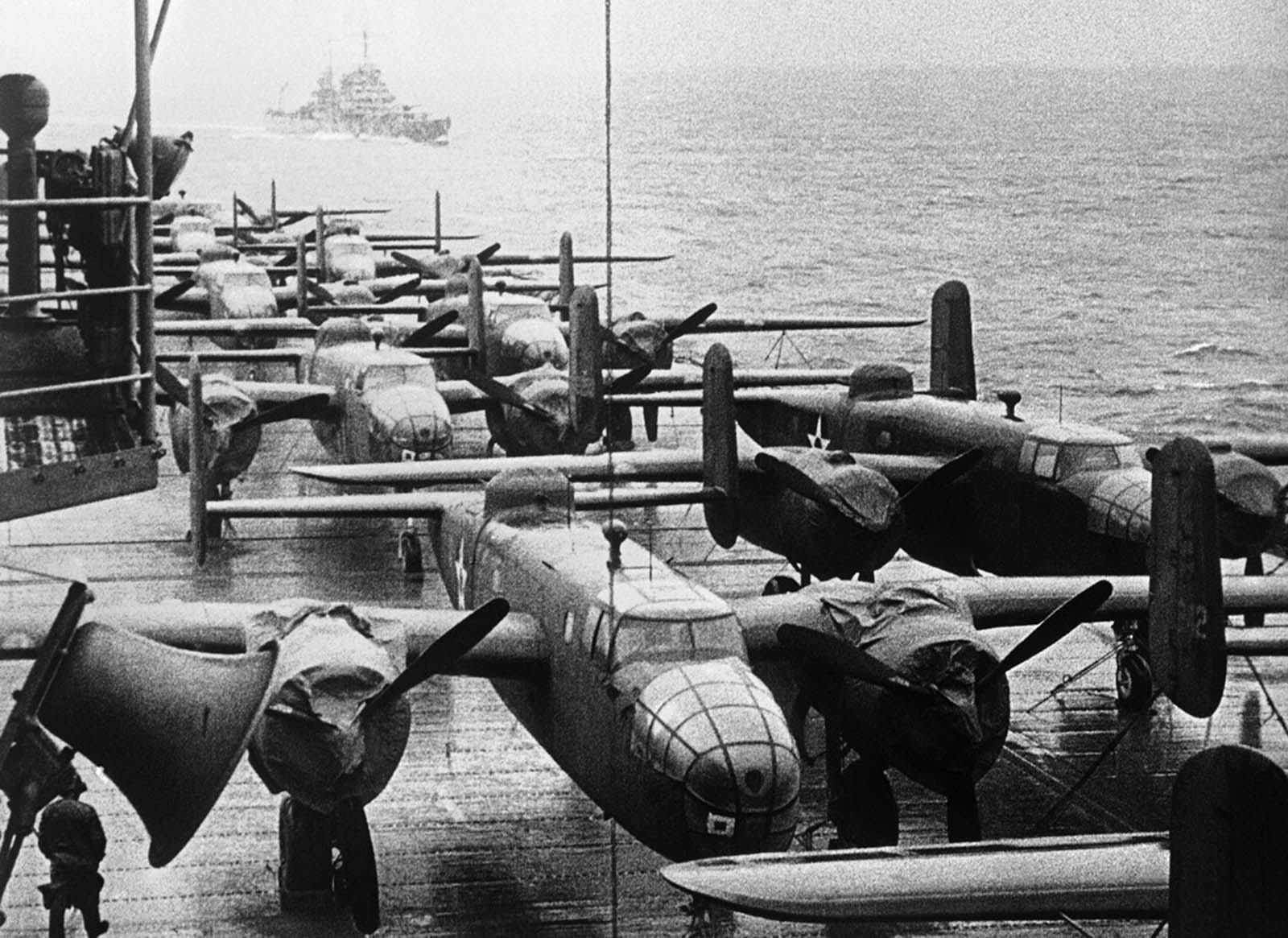 American B-25B bombers rest on the flight deck of the USS Hornet, approaching the spot where the planes were launched on their raid on Tokyo, April 13, 1942. Escort ship in left background.