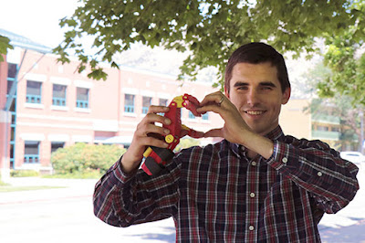 Dan makes a heart shape with his hand and a 3D printed prosthetic hand