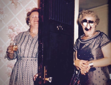 Snapshot of two old freinds, one with a Groucho Marx disguise comes through the door as her friend holds a drink.Good Heavens and Other stories of Matronly Women. marchmatron.com