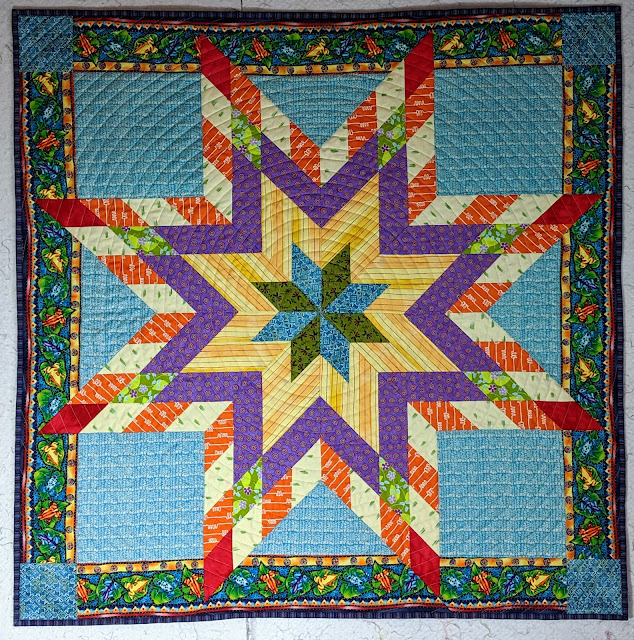 Blue, green, yellow, purple, orange, and red fabrics create a modern Lone Star set on a turquoise print background. The navy border is printed with colorful frogs and the corners are another blue print.