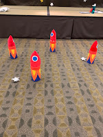 4 red and blue plush rockets on floor next to stars