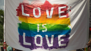 A picture of a grey t-shirt with love is love in white bold chunky font with rainbow colours behind the words like a shadow on a bright background