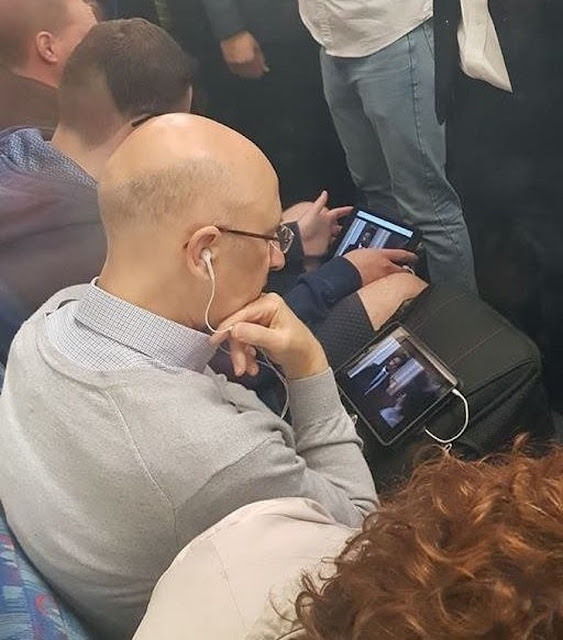 Dois homens lado a lado no ônibus assistindo ao mesmo show