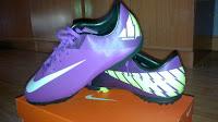 Botas de futbol nike de color violeta con dibujos amarillos y el logo blanco. Ambas botas encima de su caja.