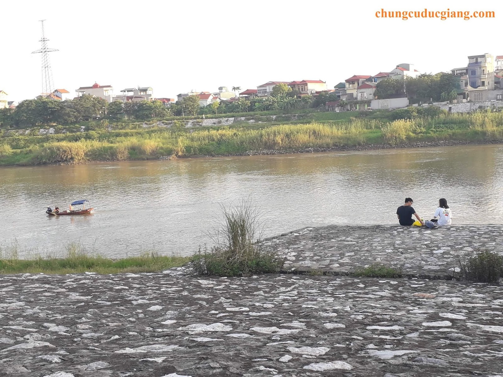 Đôi bạn trẻ đang tâm sự bên sông.