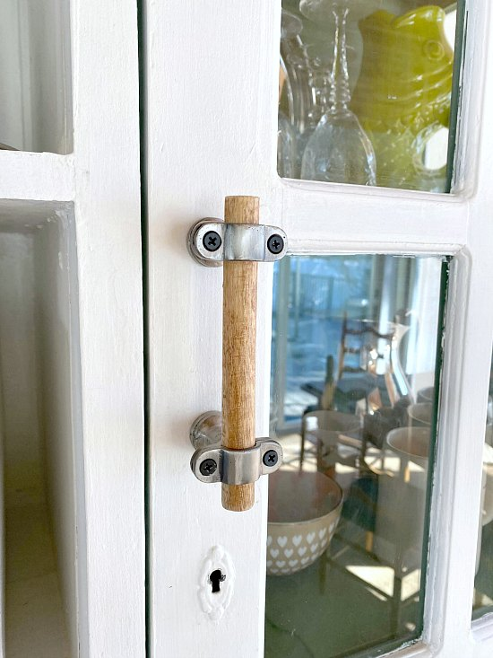 Wooden handle on white hutch