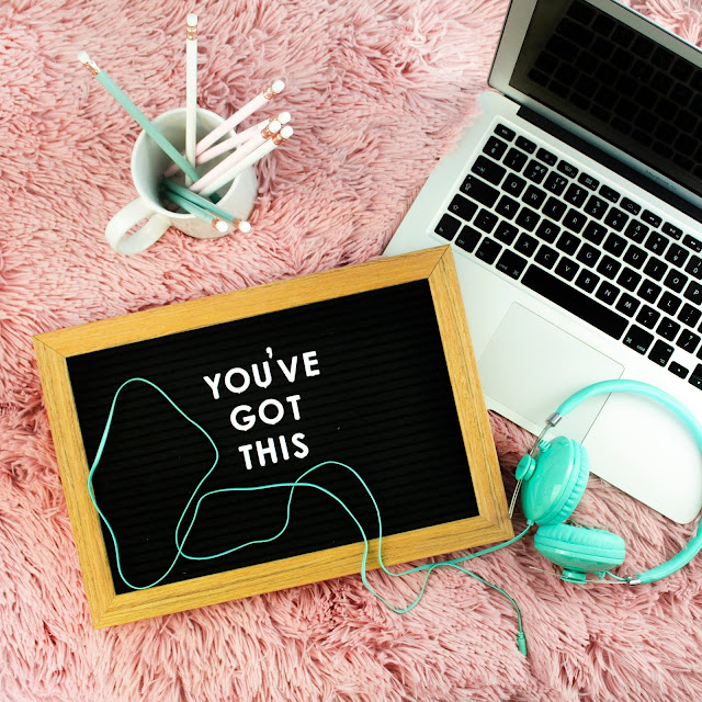 Laptop on a pink rug, next to a pot of pens, headphones and a board that reads 'you got this'