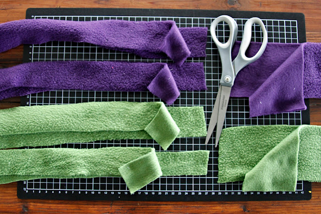 Strips of purple and green polar fleece on a cutting matt for making dog tug toys