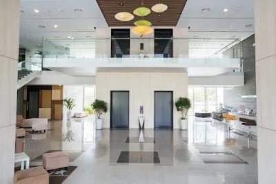 Imagem do hall decorado de um condomínio com dois elevadores lado a lado, com estofados e poltronas de espera, mezanino com acesso por escada lateral.