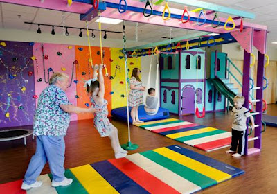 Photo of a typical sensory room with swings and padded colorful flooring and kids at play with an instructor