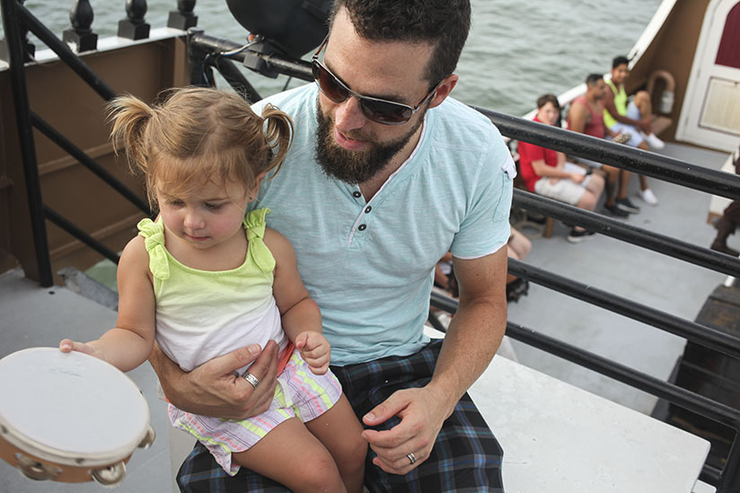 Father and daughter play with a tambourine aboard the Black Raven Pirate Ship
